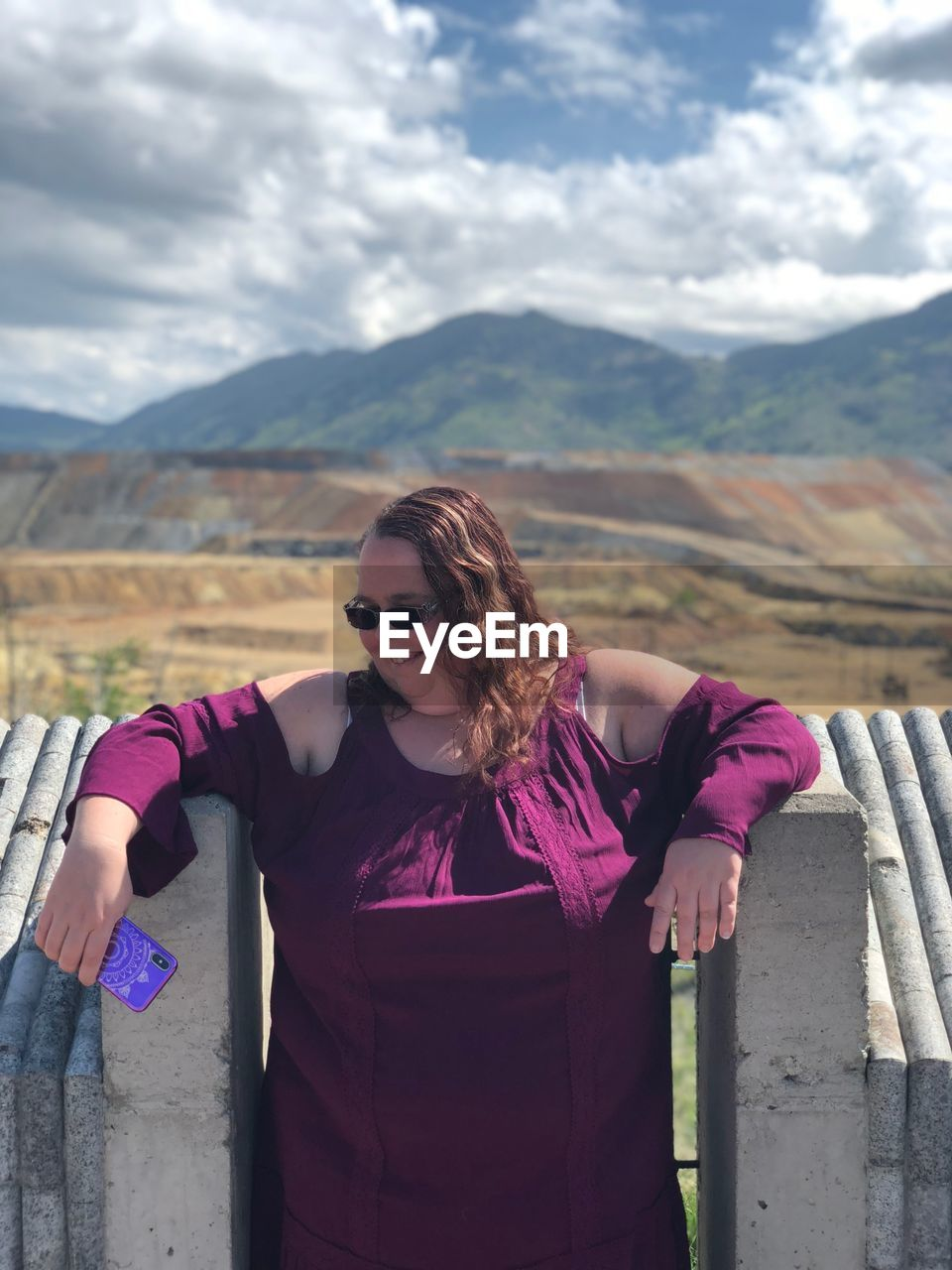 Overweight woman wearing sunglasses standing against mountains