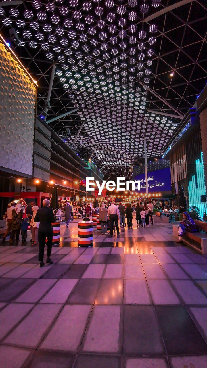 built structure, group of people, architecture, illuminated, real people, women, men, crowd, people, adult, lifestyles, indoors, night, ceiling, group, flooring, city, lighting equipment, building, modern, waiting, tiled floor, nightlife