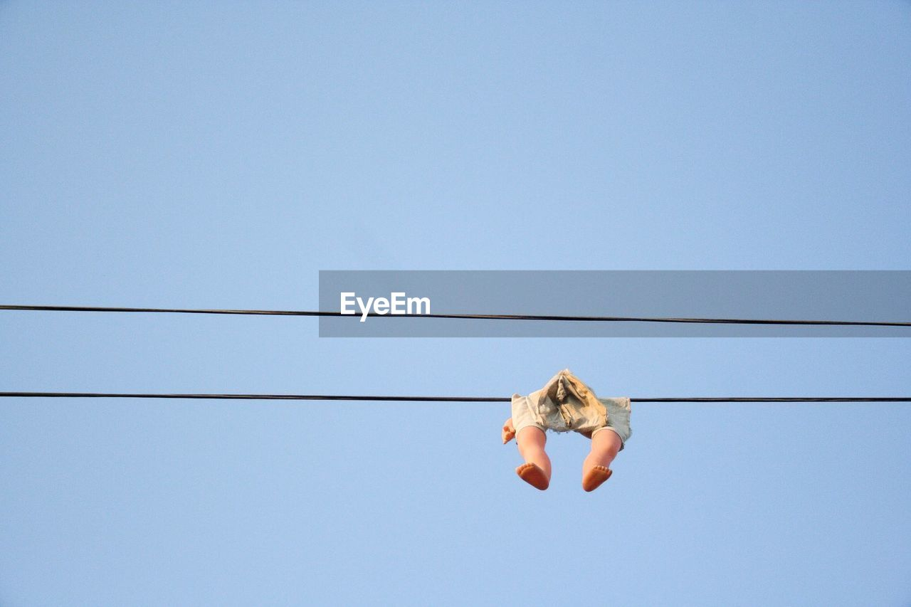 Low Angle View Of Toy Hanging From Cable Against Clear Sky