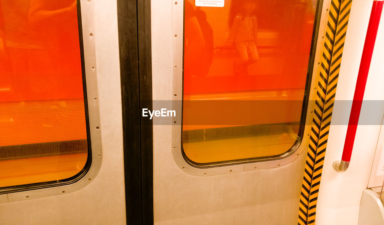 mode of transportation, transportation, public transportation, window, no people, rail transportation, train, train - vehicle, vehicle door, orange color, travel, vehicle interior, transparent, outdoors, white color, glass - material, day, close-up, red, metal, subway train