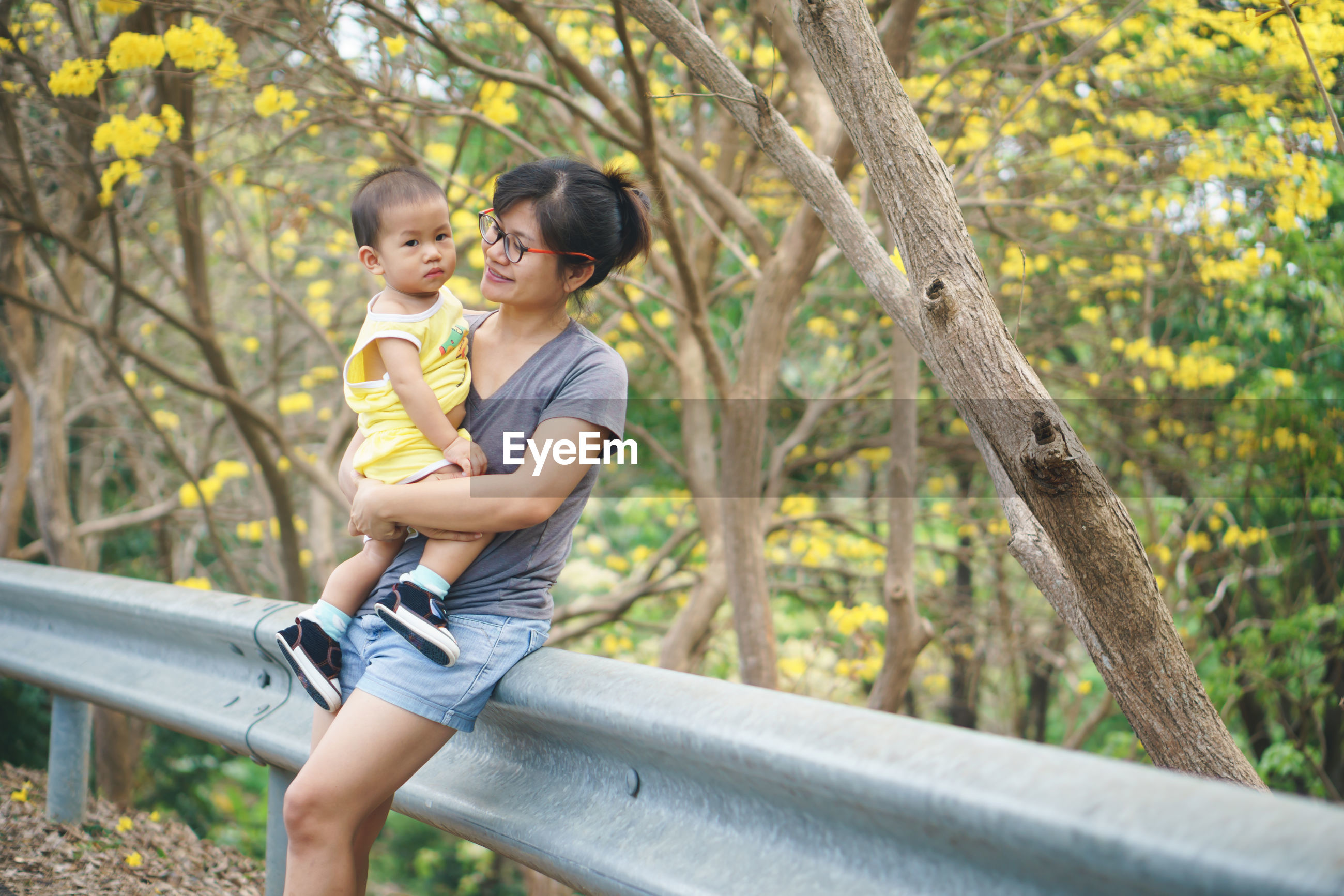 Smiling woman with son leaning on railing in forest