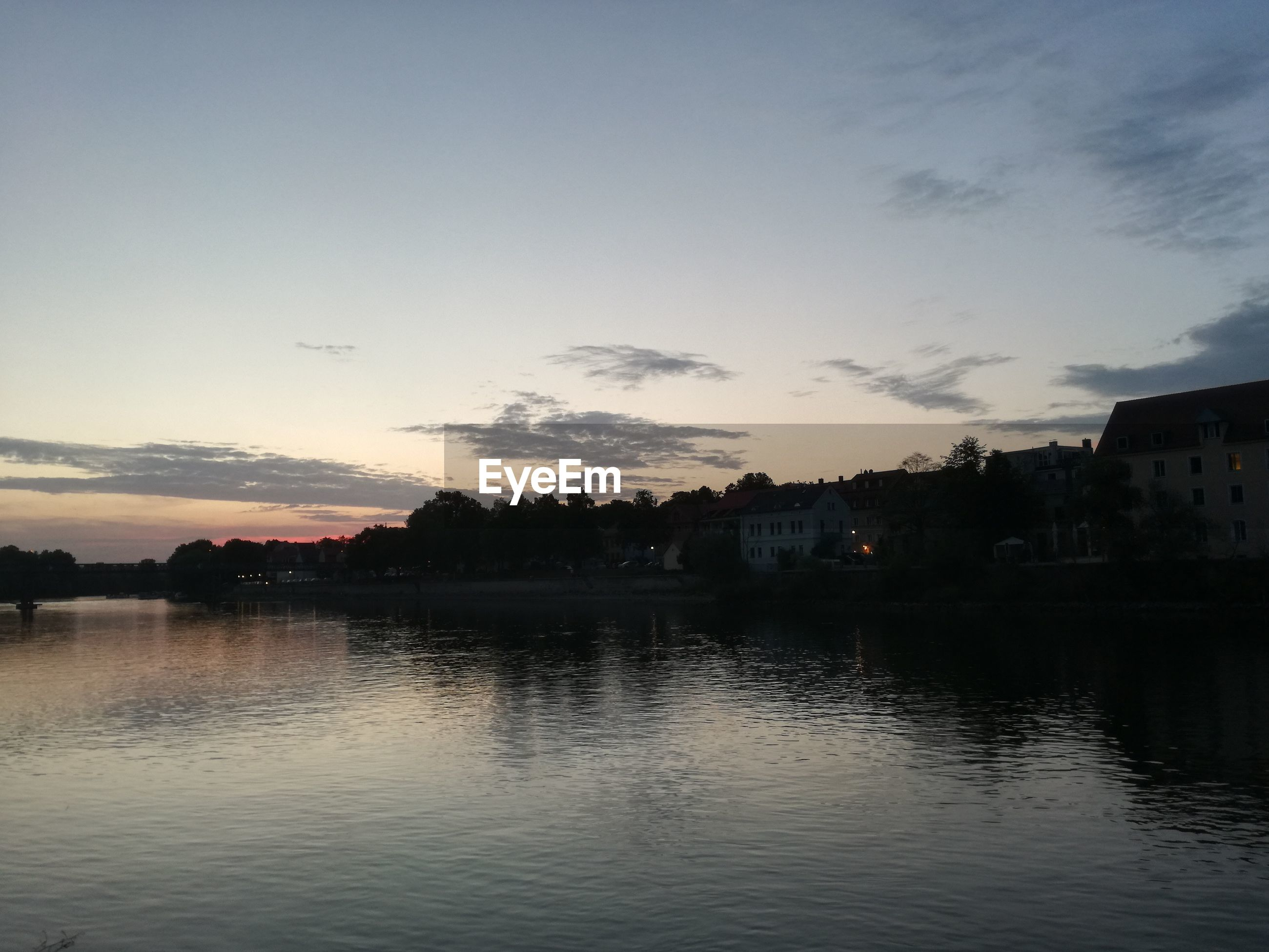 Scenic view of river in city against sky during sunset