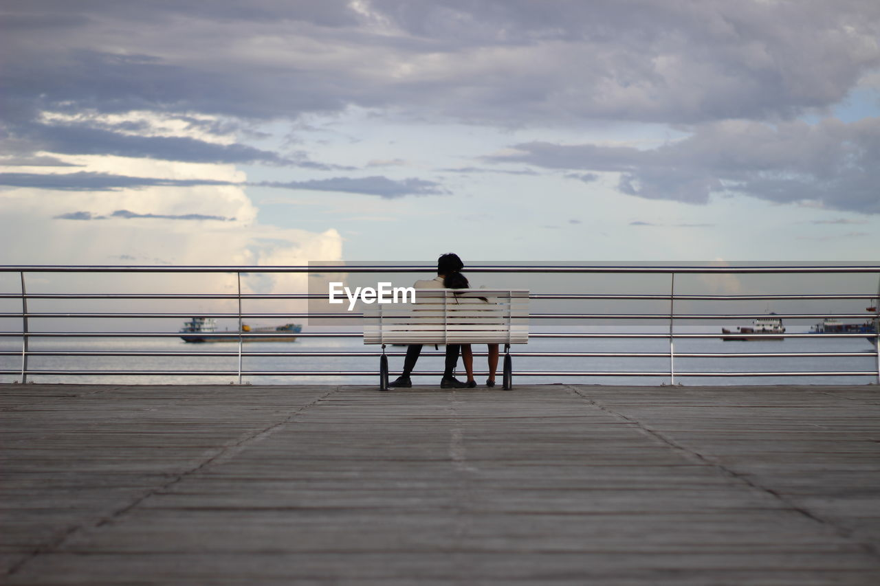 Rear view of couple sitting on bench by railing against sky