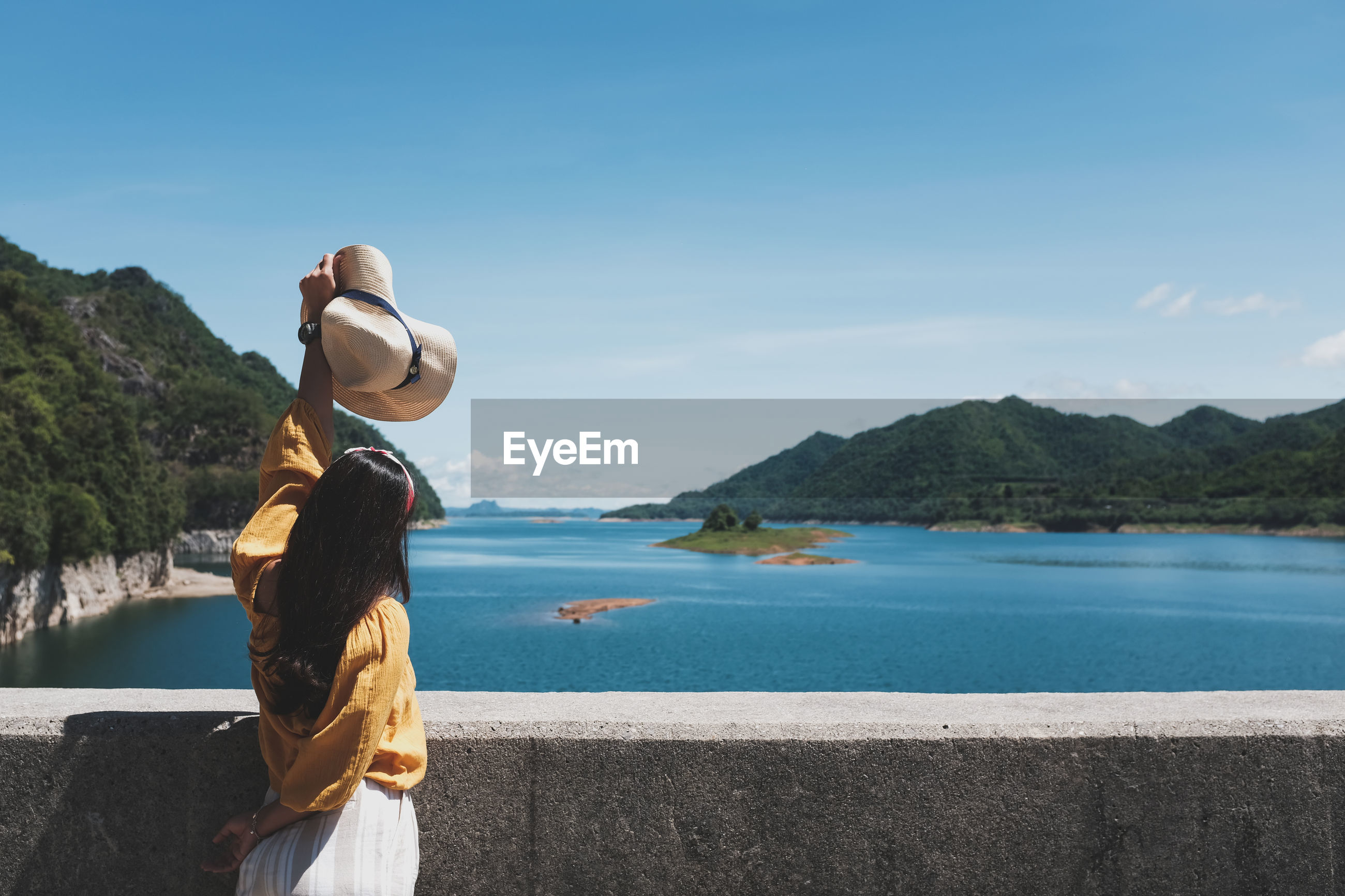 The back of a female tourist and holding a hat the background is rivers and mountains