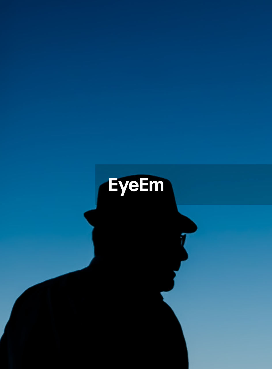 Low Angle View Of Silhouette Man Wearing Hat Against Clear Blue Sky During Dusk