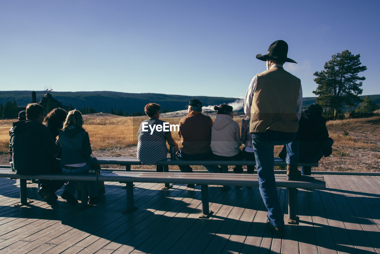 Rear View Of People Sitting On Bench At Yellowstone National Park Against Clear Sky