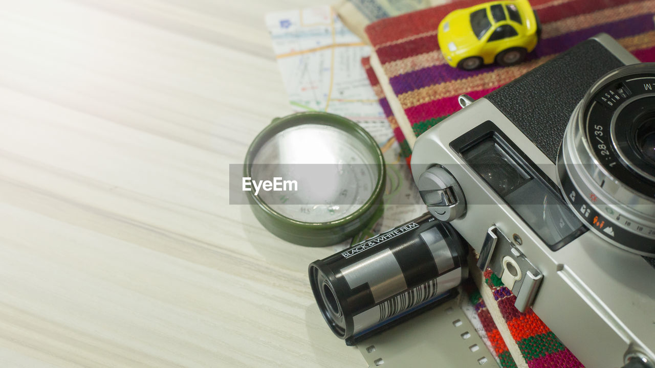 High angle view of technologies and travel equipment on wooden table