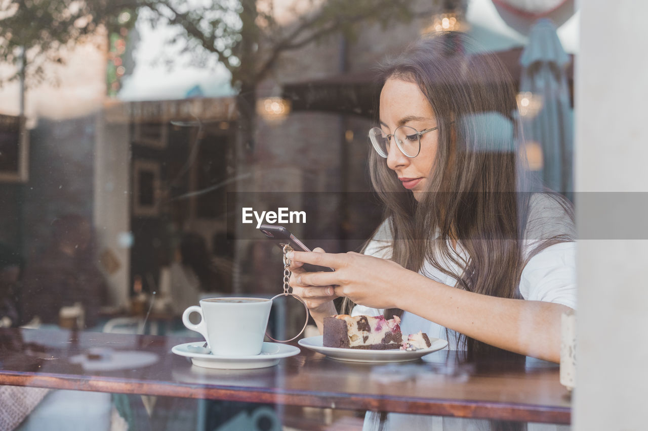 WOMAN HOLDING COFFEE CUP ON TABLE IN CAFE AT HOME