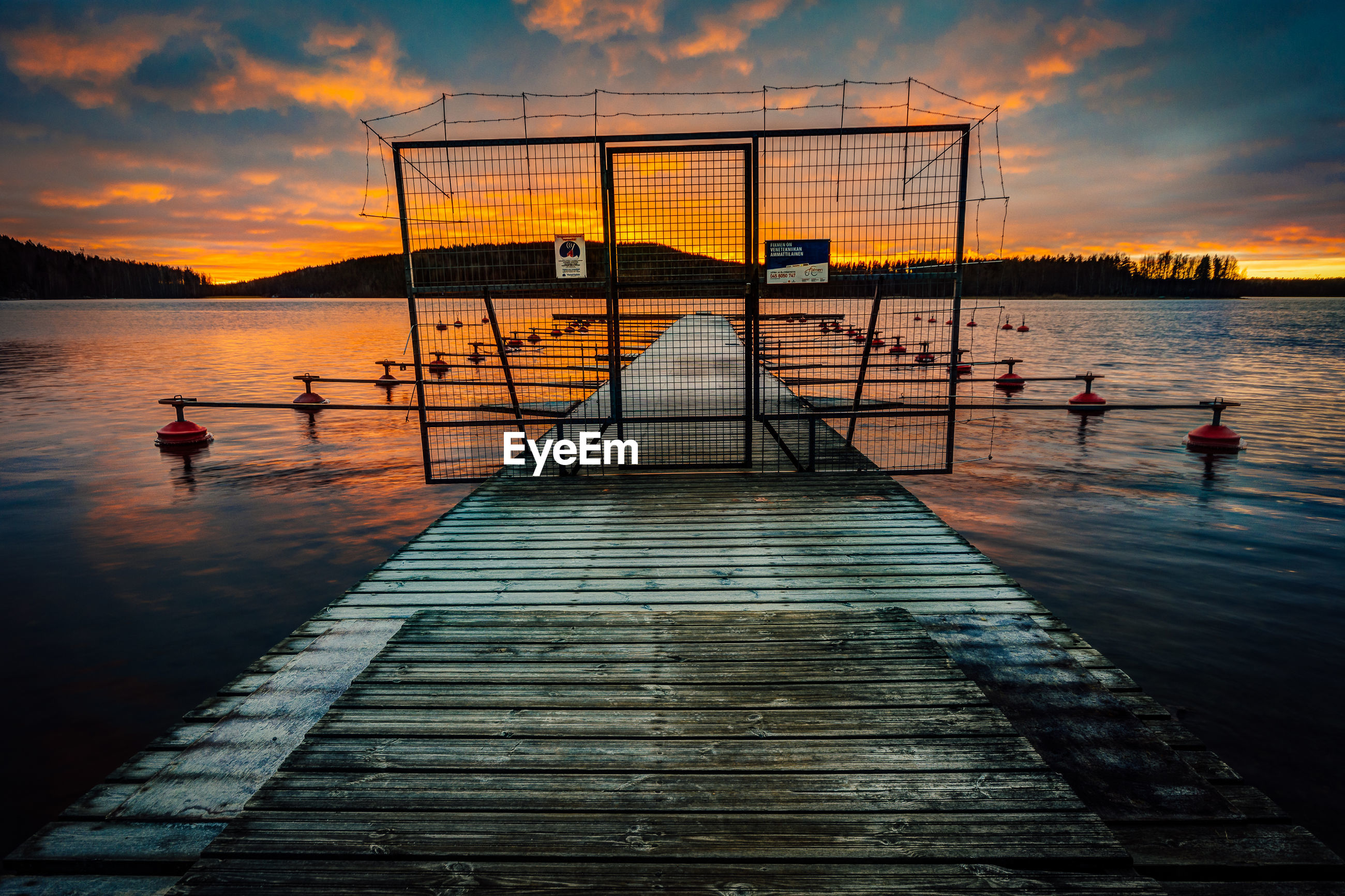 Closed gate on jetty amidst lake against sky during sunset