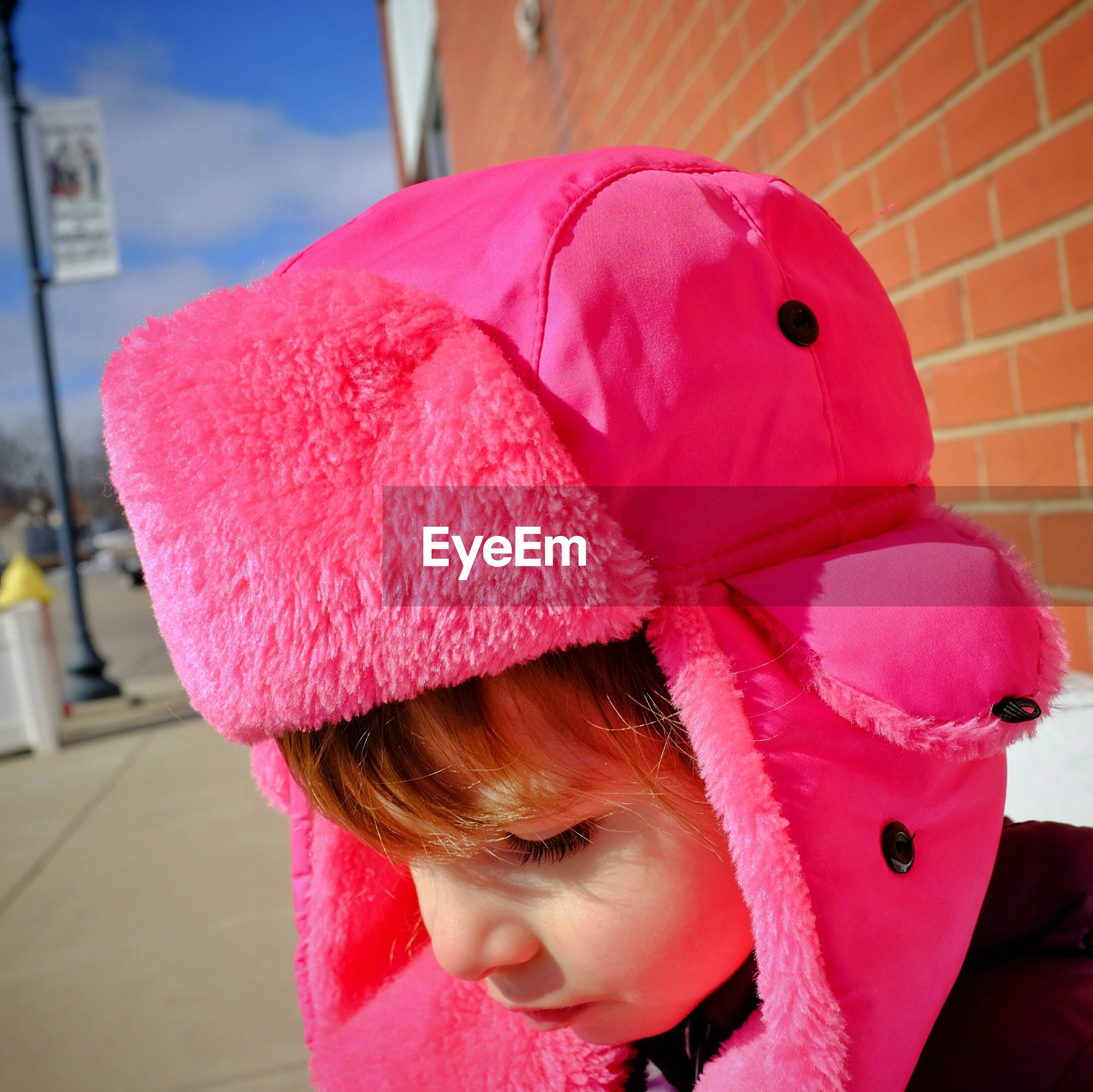 Close-up of a boy in pink hat looking down