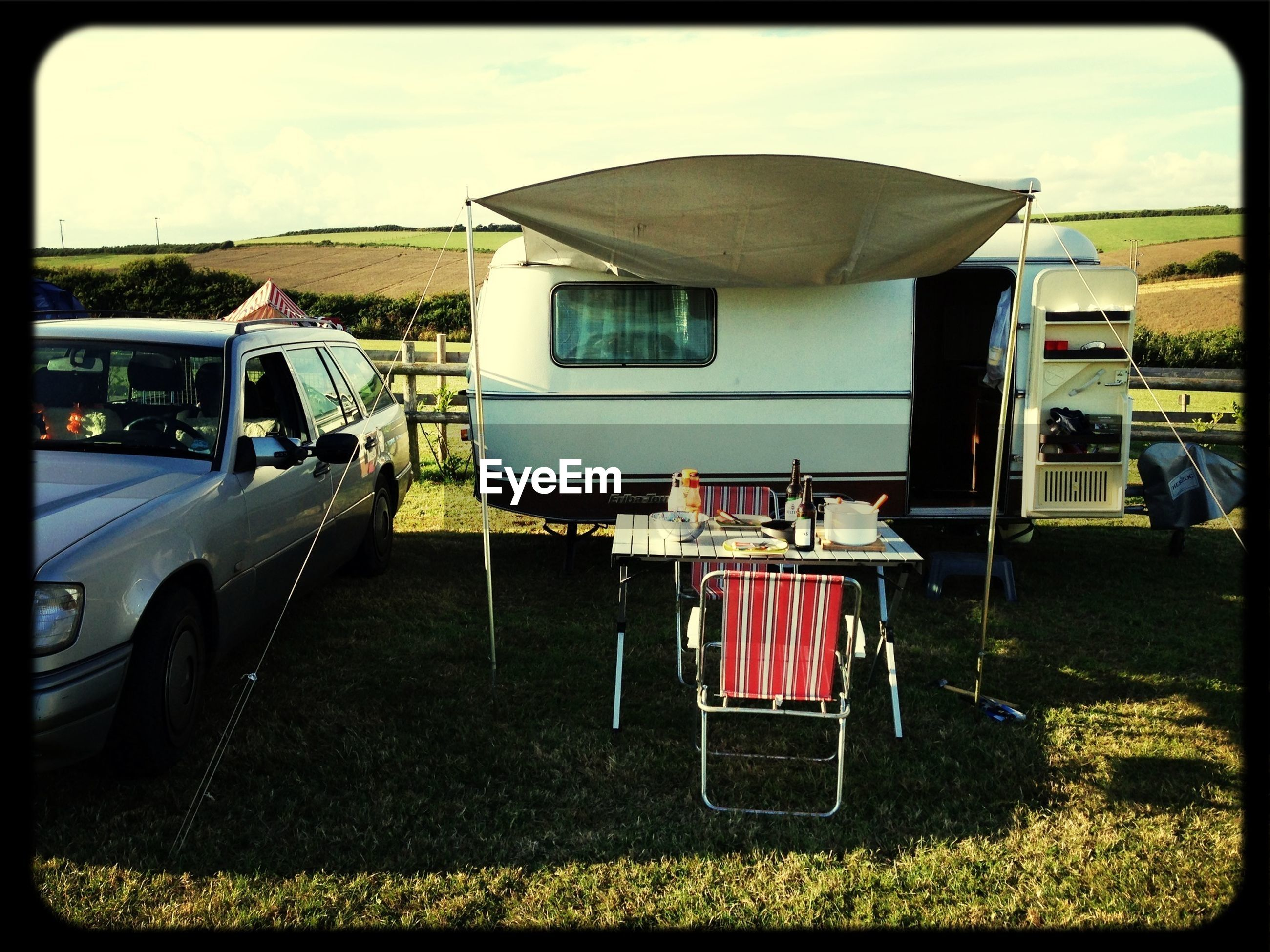 Trailer home and car with table setting on field