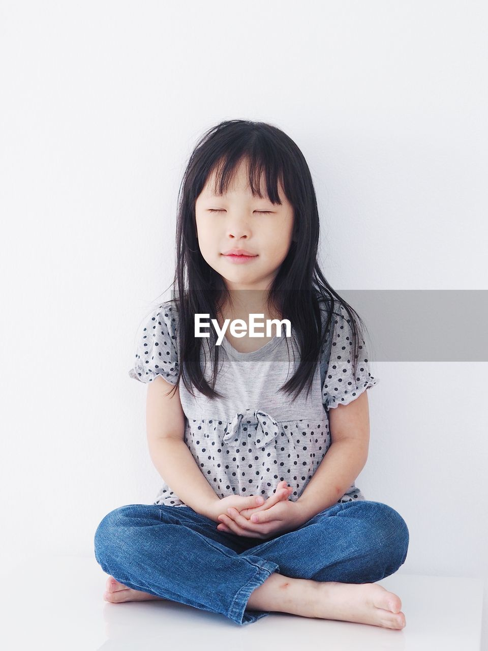 Girl with closed eyes sitting against white background