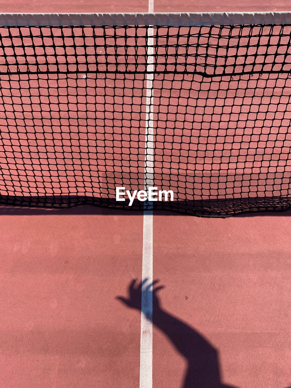 Shadow of hand on tennis court