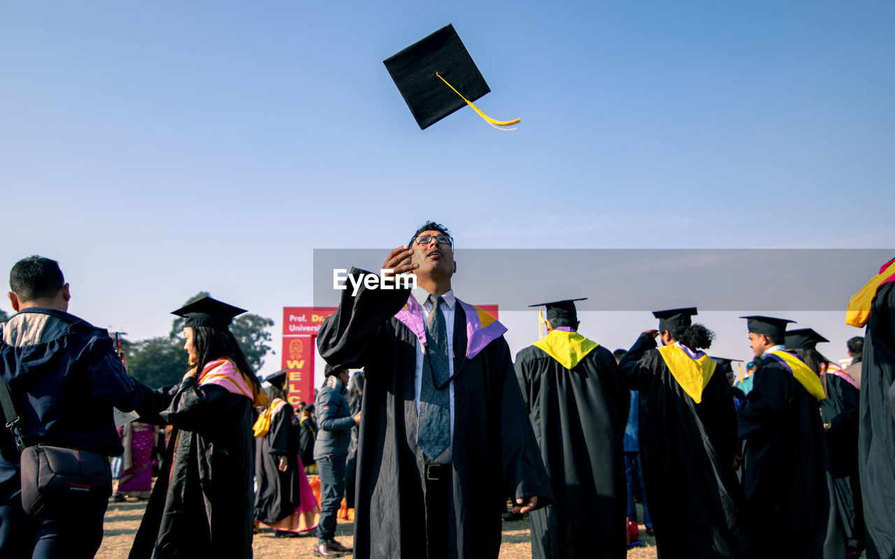 Man looking up while throwing mortarboard in sky