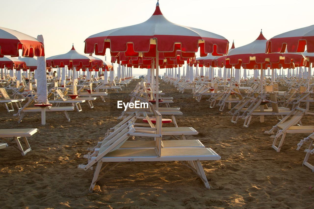 Deck Chairs With Parasols On Beach Against Sky
