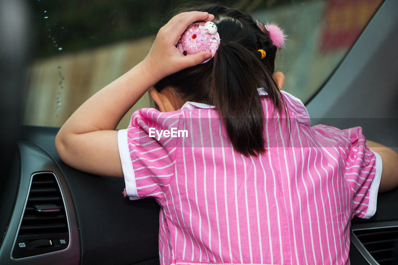 Rear view of girl sitting in car