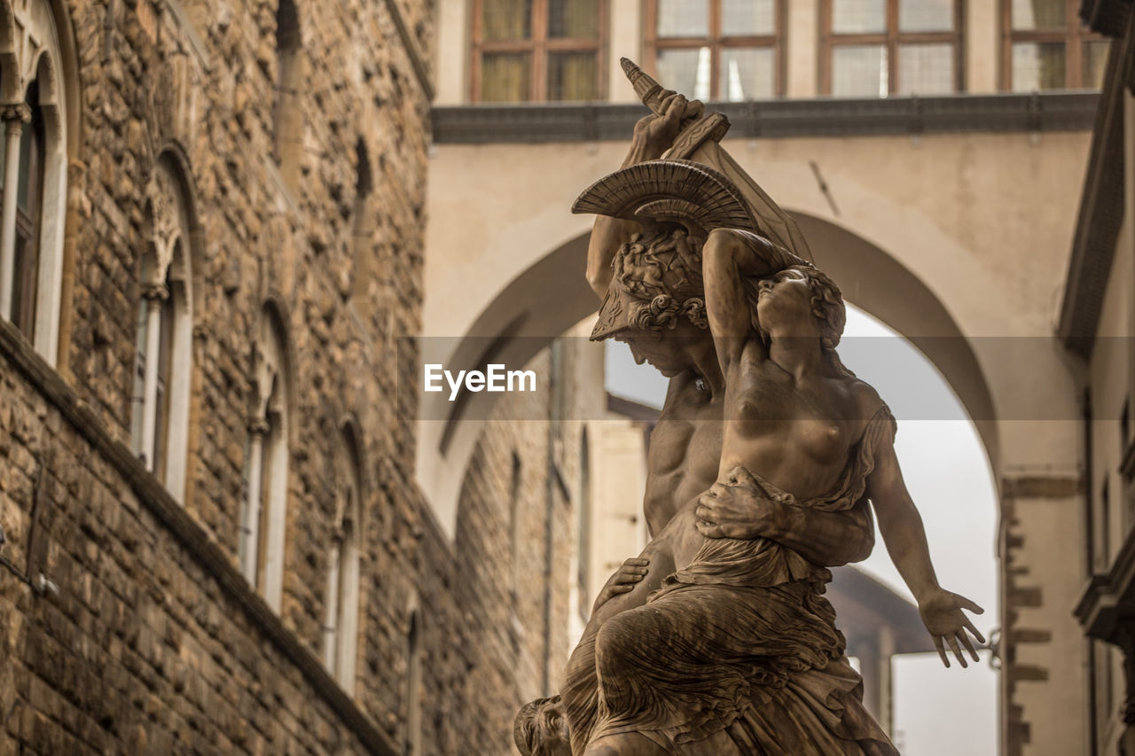 statue, sculpture, human representation, architecture, art and craft, built structure, building exterior, male likeness, low angle view, outdoors, day, travel destinations, focus on foreground, no people, city