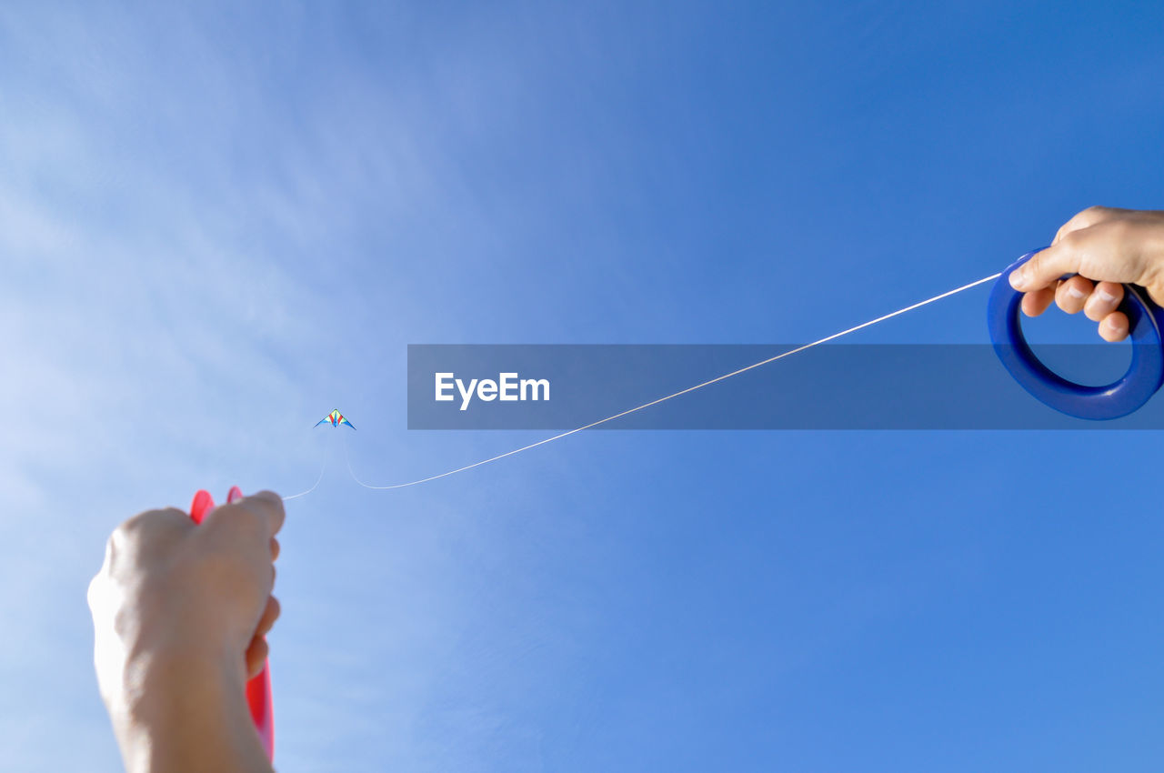 Low angle view of hand holding kite against blue sky