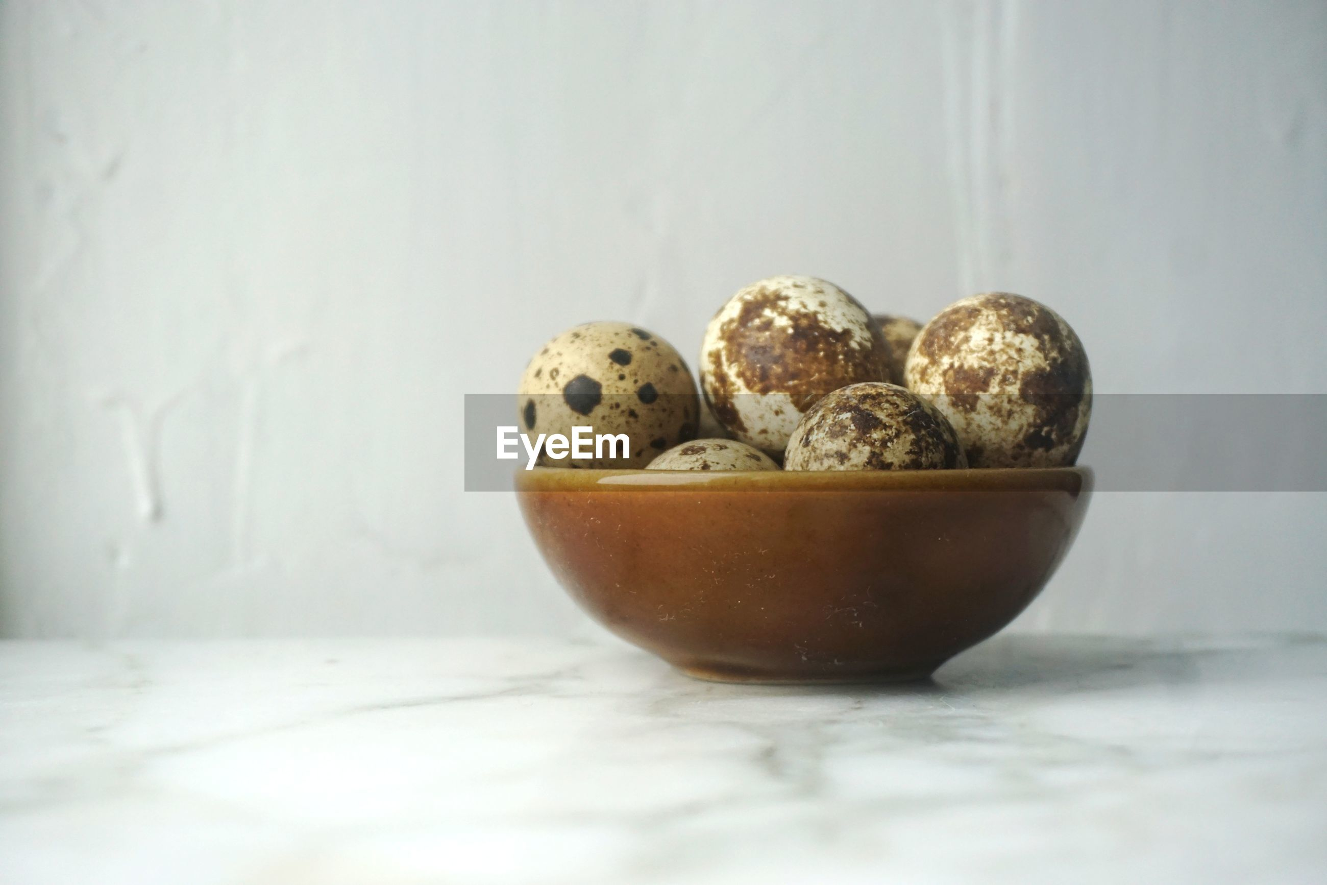 Close-up of quail eggs in bowl on marble