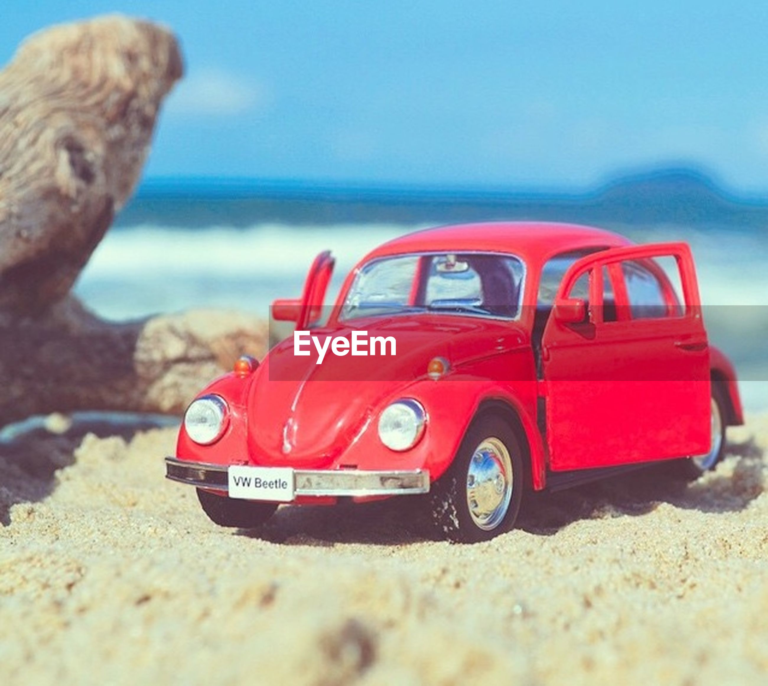 beach, sea, red, transportation, focus on foreground, horizon over water, sand, selective focus, mode of transport, shore, land vehicle, close-up, toy, sky, surface level, clear sky, sunlight, day, outdoors, sunglasses