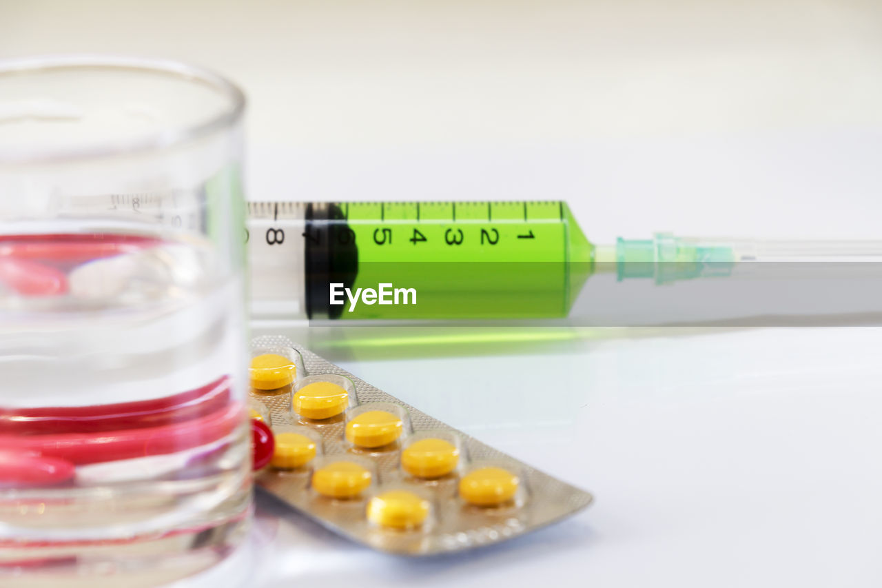 Close-up of pills with syringe on table