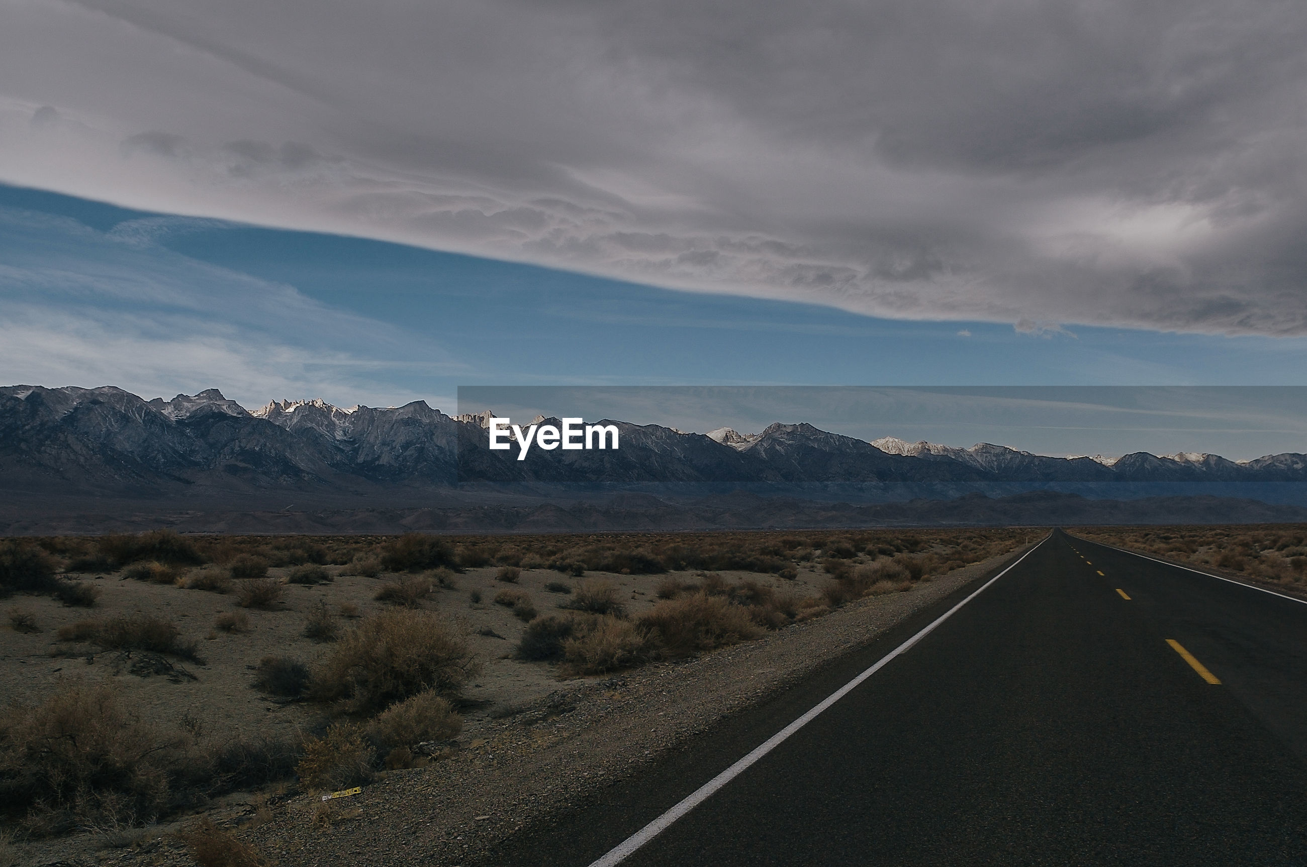 Empty road amidst landscape leading towards mountains against cloudy sky