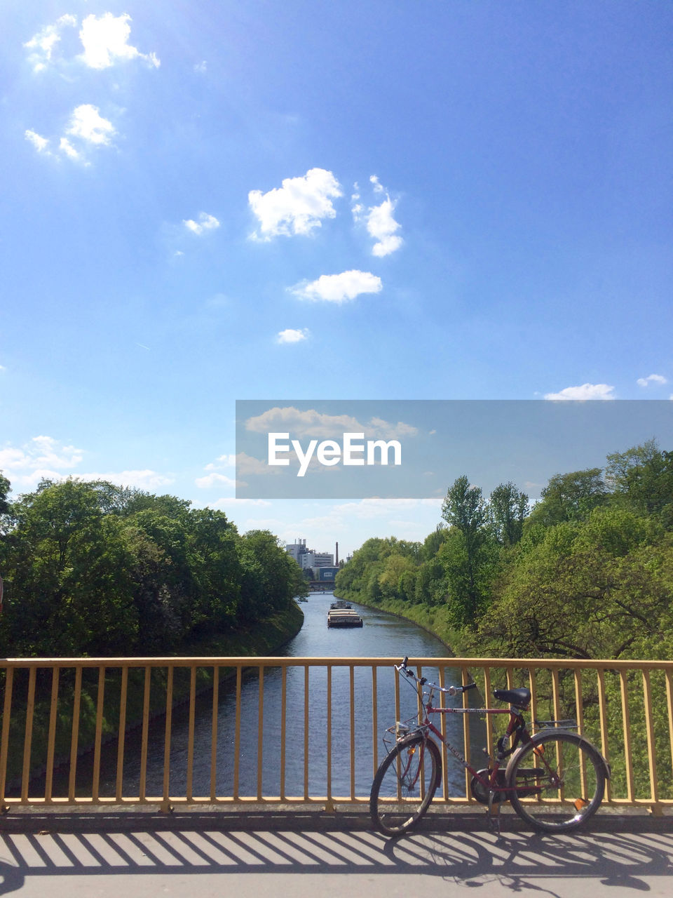 sky, railing, tree, cloud - sky, bicycle, day, bridge - man made structure, outdoors, river, water, transportation, built structure, architecture, mode of transport, nature, no people, sunlight, travel destinations, building exterior, city, footbridge, beauty in nature