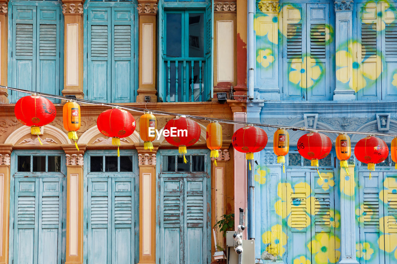 Low Angle View Of Chinese Lanterns Hanging Against Building