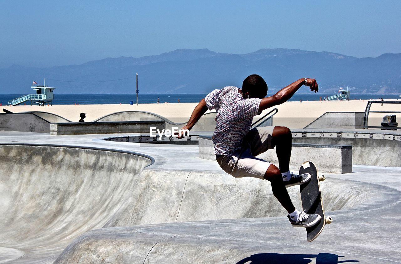 Full Length Of Man Skateboarding In Park Against Clear Sky At Beach