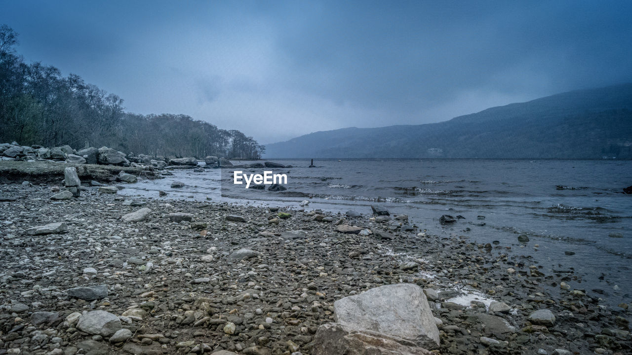 water, sky, mountain, beauty in nature, scenics - nature, tranquility, tranquil scene, nature, cloud - sky, no people, day, rock, non-urban scene, land, solid, beach, lake, environment, outdoors, pollution