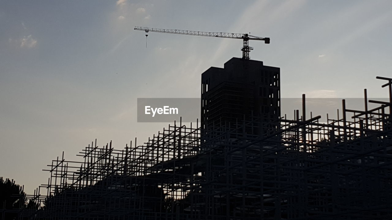 LOW ANGLE VIEW OF SILHOUETTE CRANES AGAINST BUILDINGS