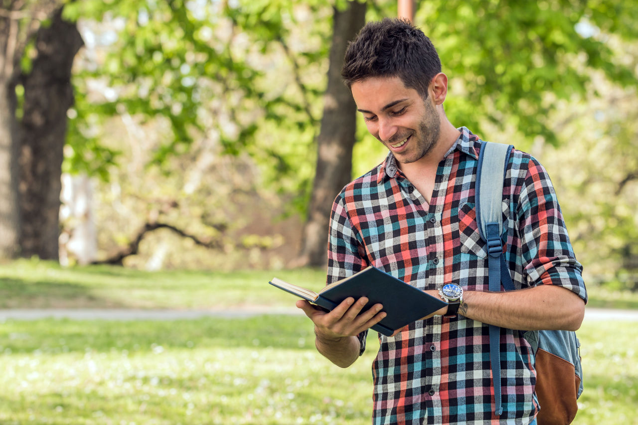Smiling young man reading book while standing against trees in park