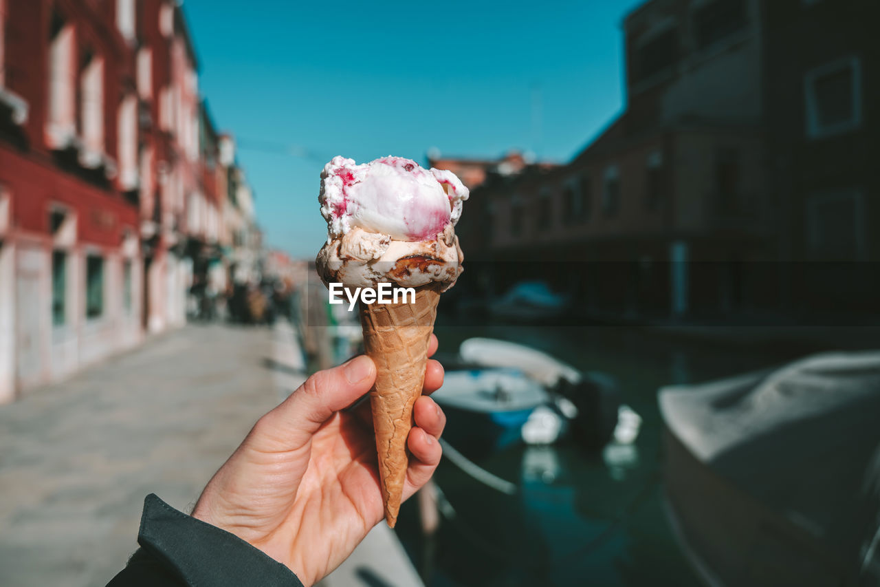 ice cream, frozen, frozen food, sweet, ice cream cone, sweet food, holding, human hand, dessert, hand, one person, cone, unhealthy eating, indulgence, dairy product, temptation, food, food and drink, human body part, focus on foreground, outdoors, finger, frozen sweet food