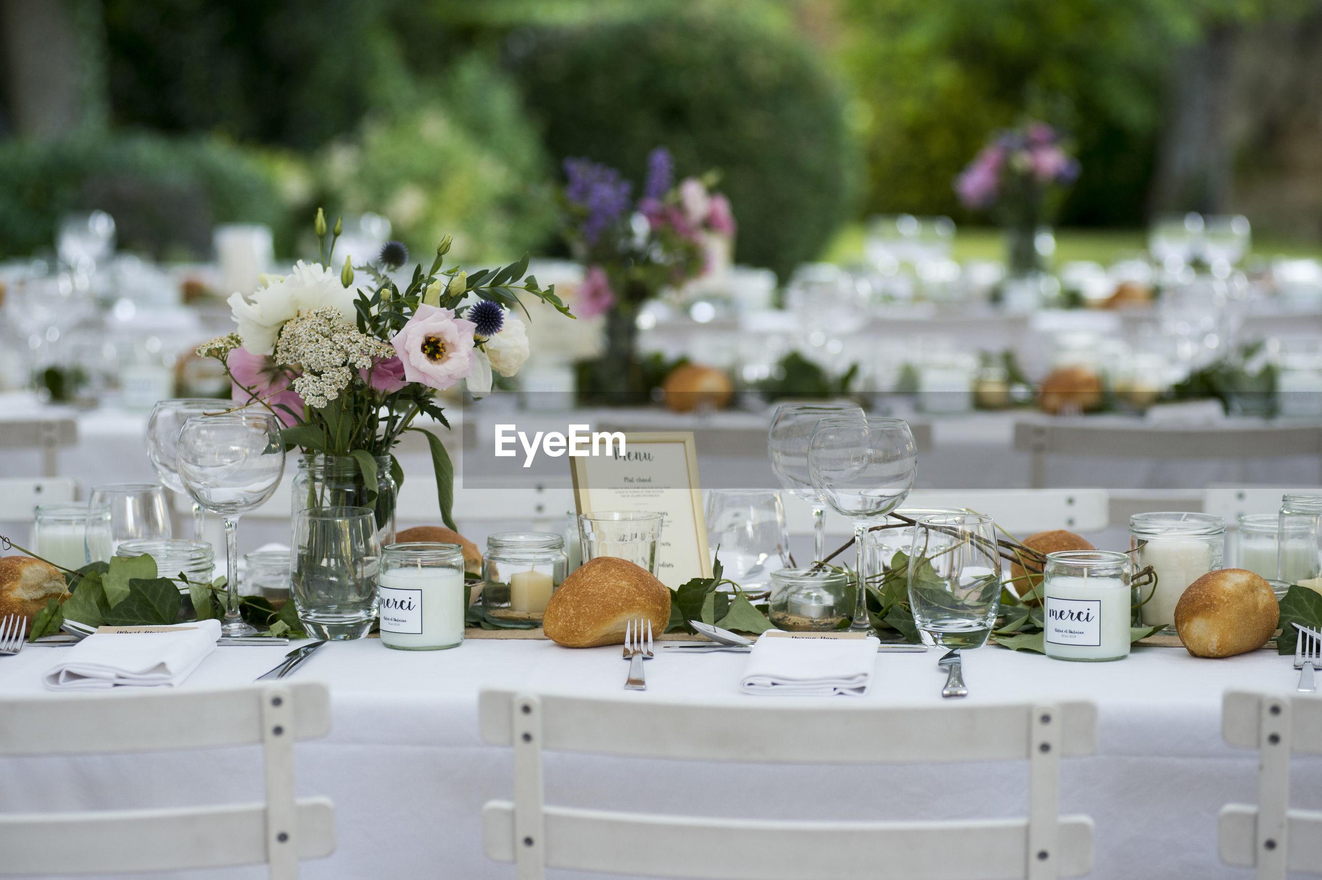 FLOWERS IN VASE ON TABLE AGAINST PLANTS