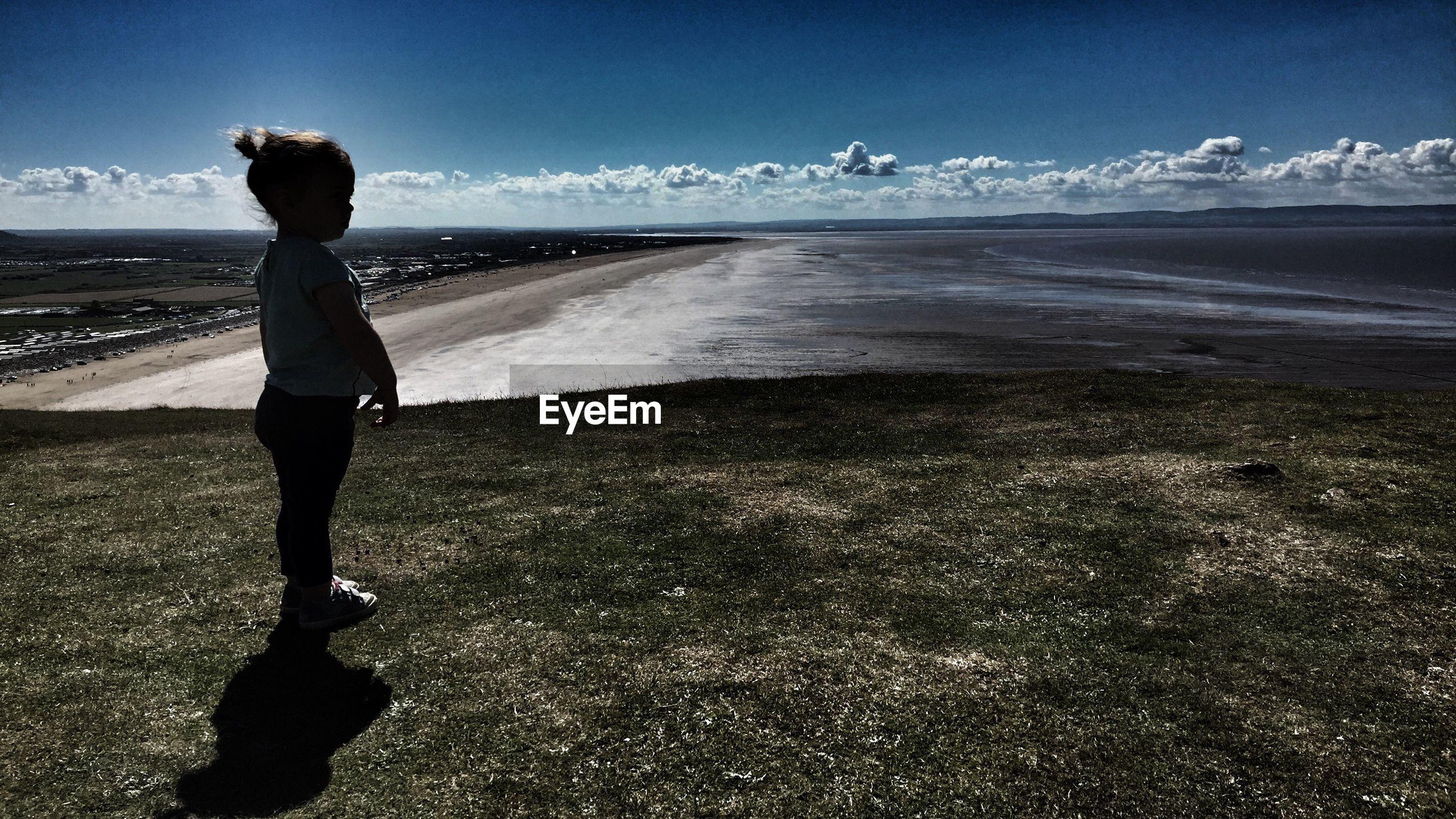Girl standing at beach against sky