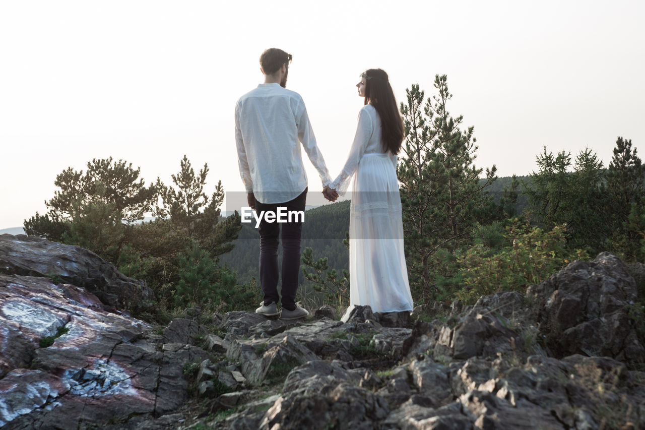 two people, togetherness, love, full length, women, rock, couple - relationship, rock - object, nature, sky, solid, young men, young women, bonding, young adult, men, rear view, standing, people, emotion, positive emotion, outdoors