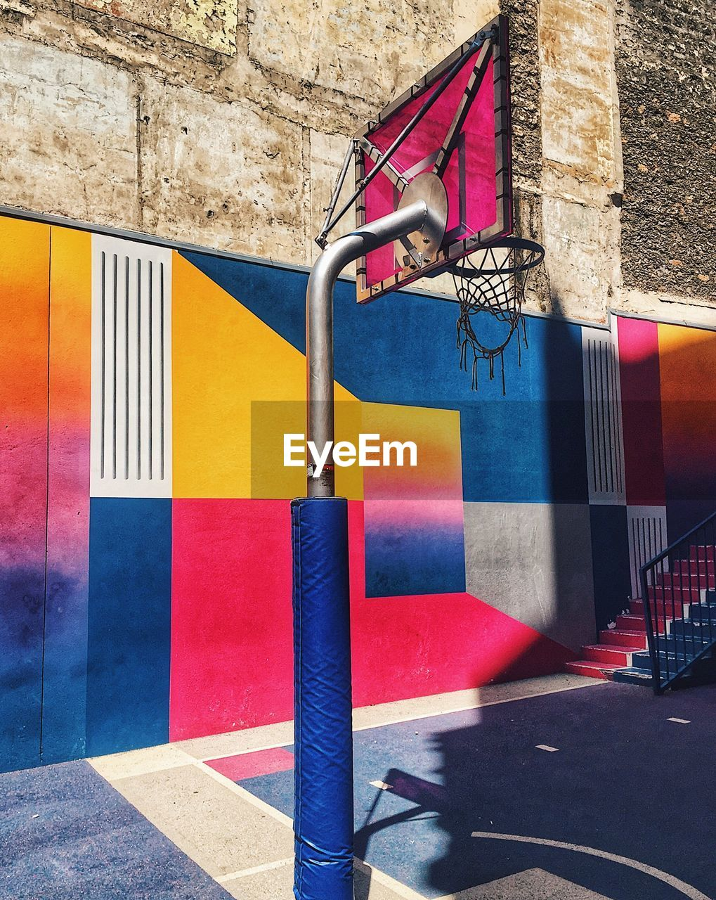 Low angle view of basketball hoop by colorful wall at sports court