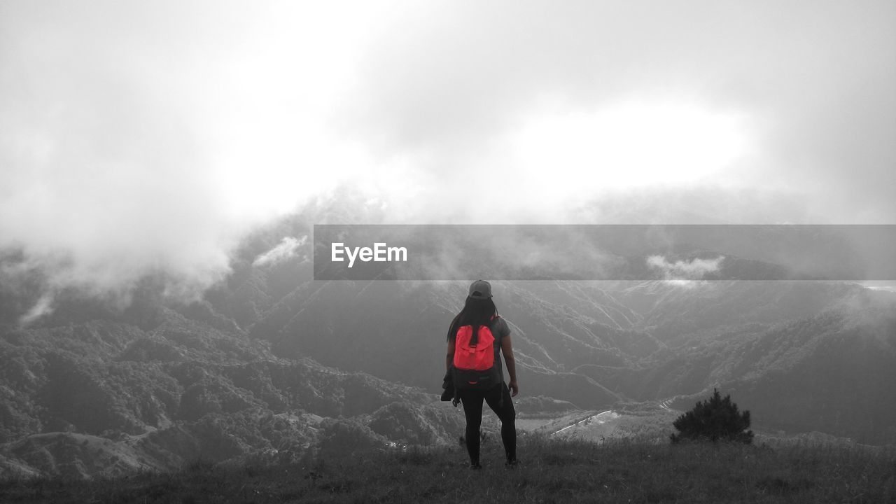 REAR VIEW OF PERSON STANDING ON MOUNTAIN AGAINST SKY