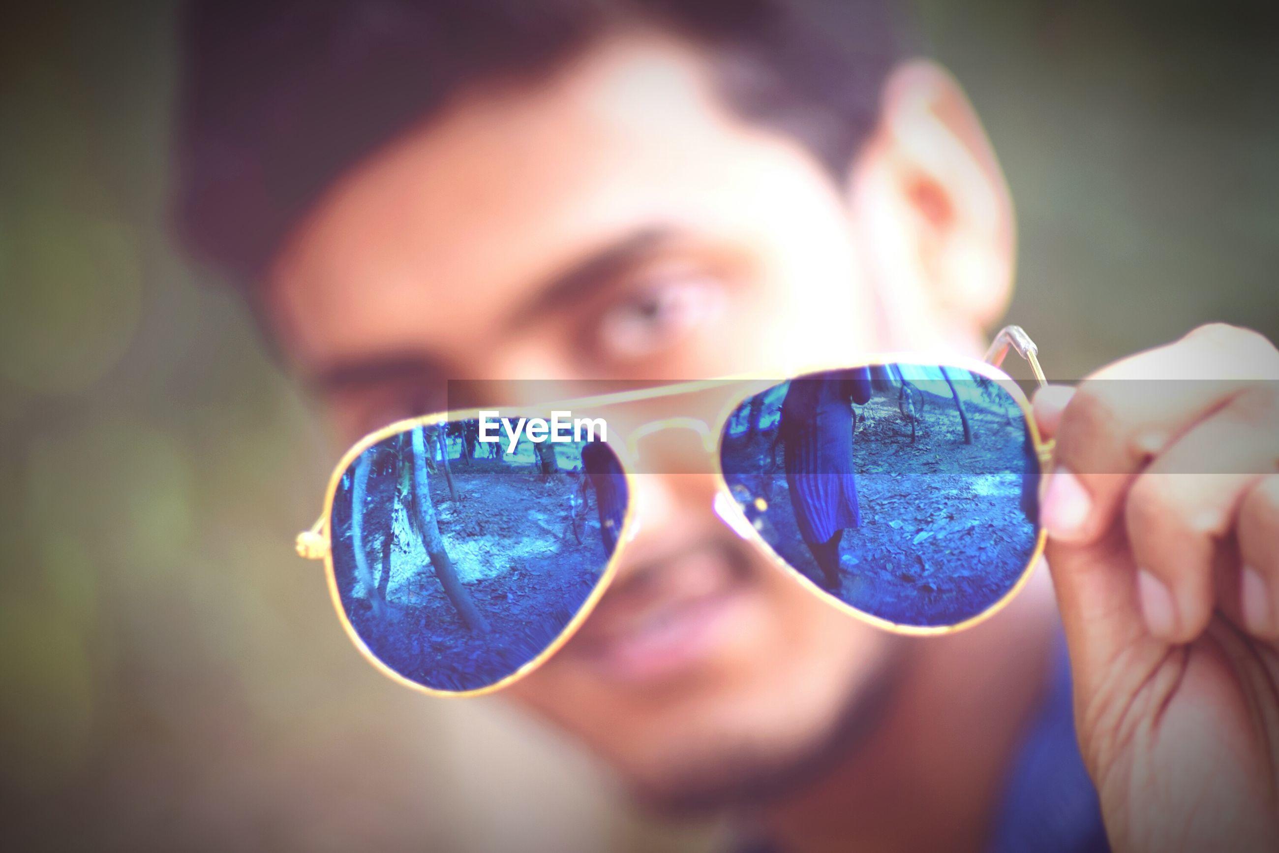 Close-up of man holding sunglasses