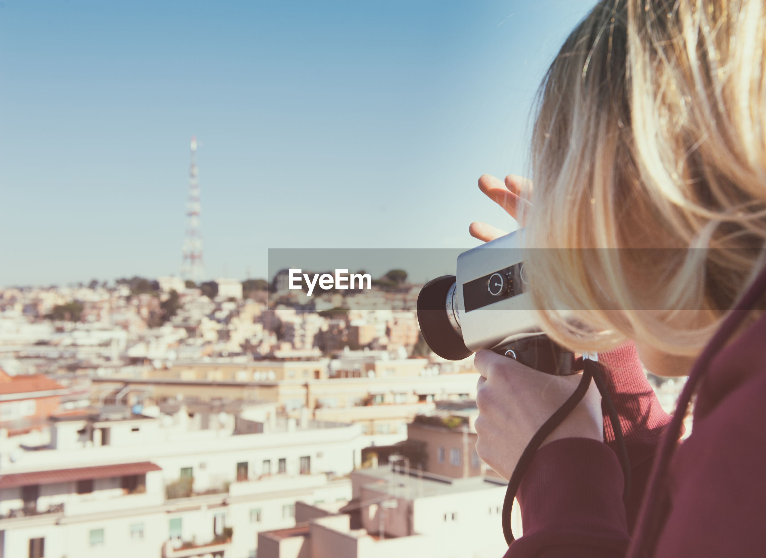 Woman photographing cityscape against clear sky