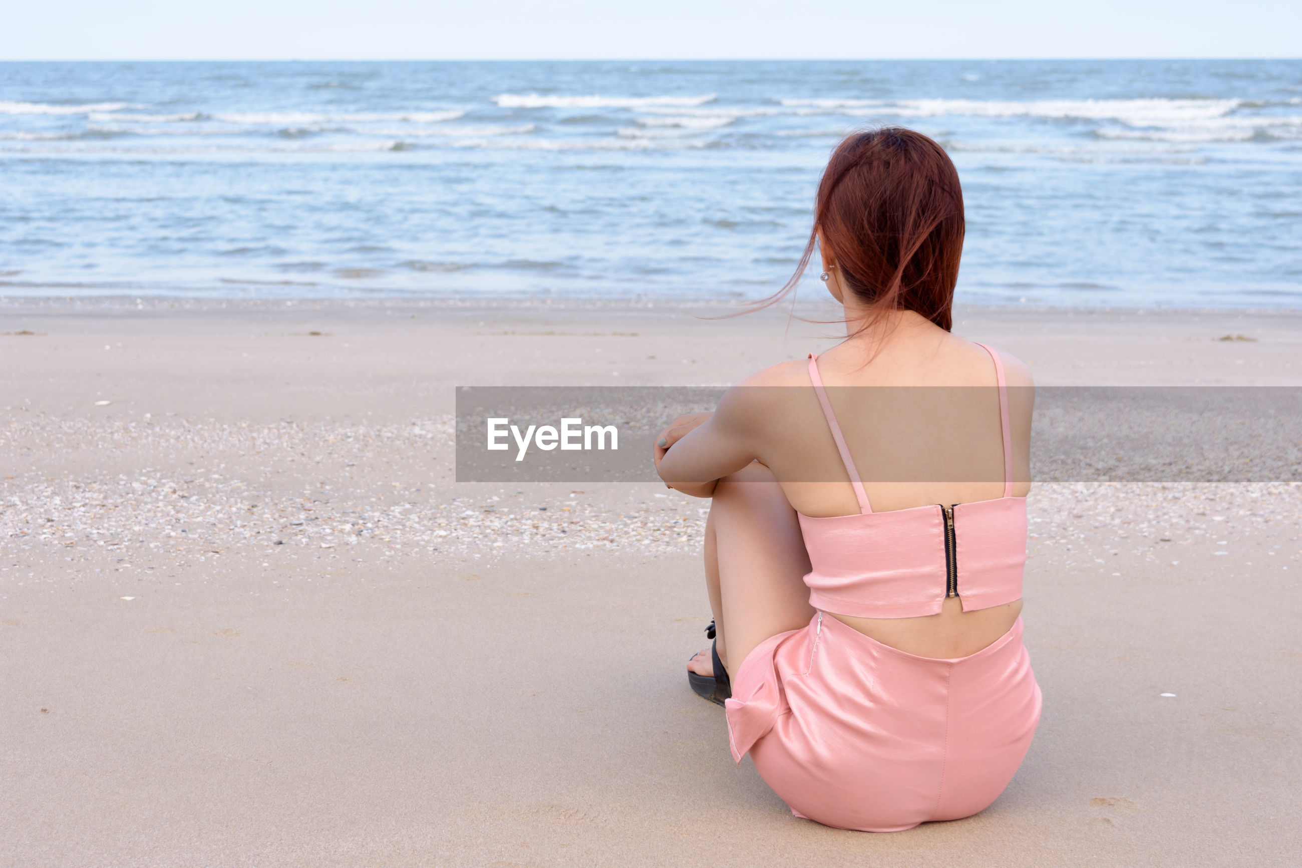 REAR VIEW OF WOMAN SITTING ON SHORE