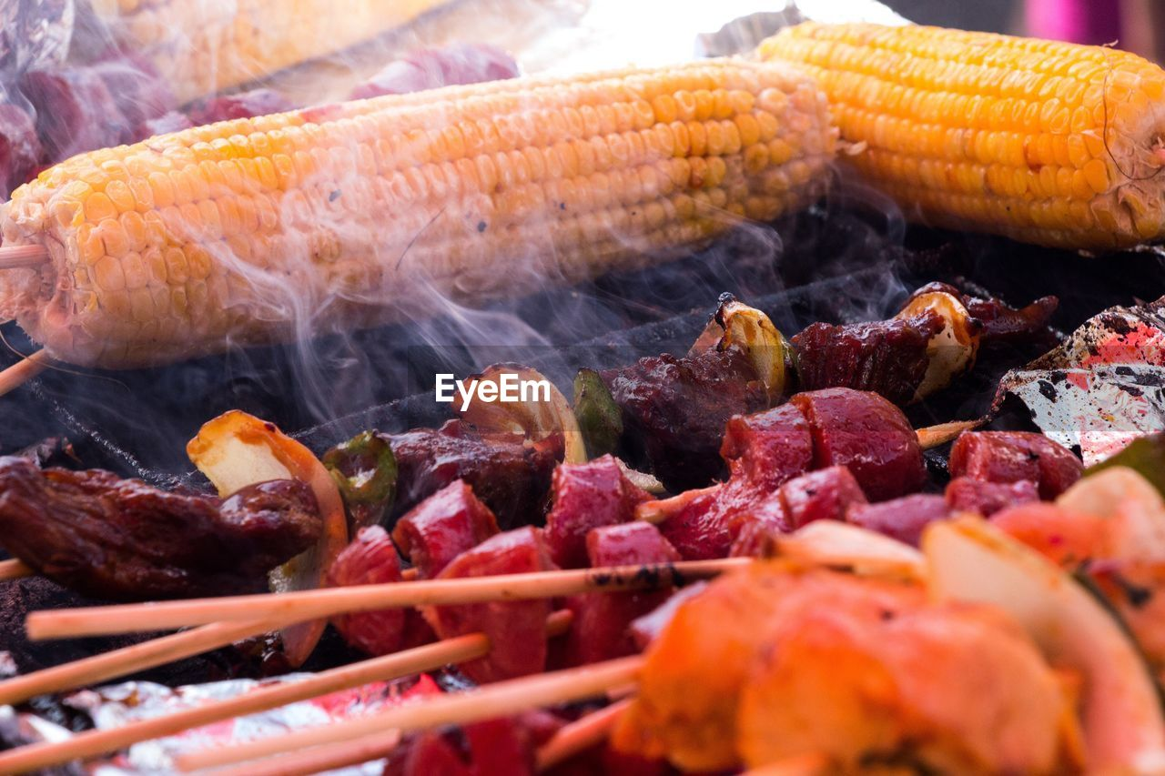 Close-Up Of Sweetcorns And Meat Cooking On Barbecue