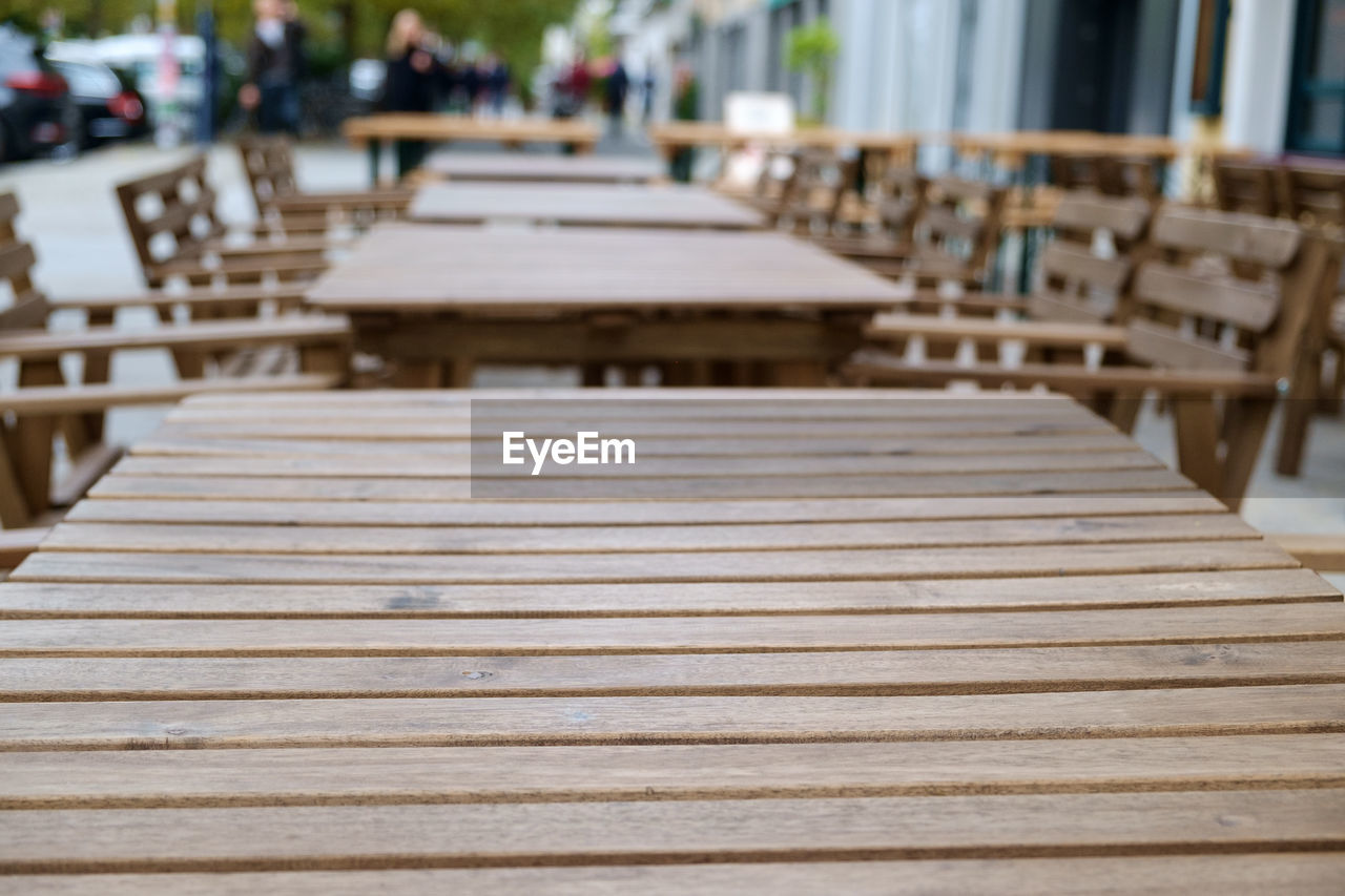 table, seat, wood - material, focus on foreground, chair, in a row, incidental people, empty, arrangement, architecture, day, business, restaurant, cafe, outdoors, absence, selective focus, direction, the way forward, setting