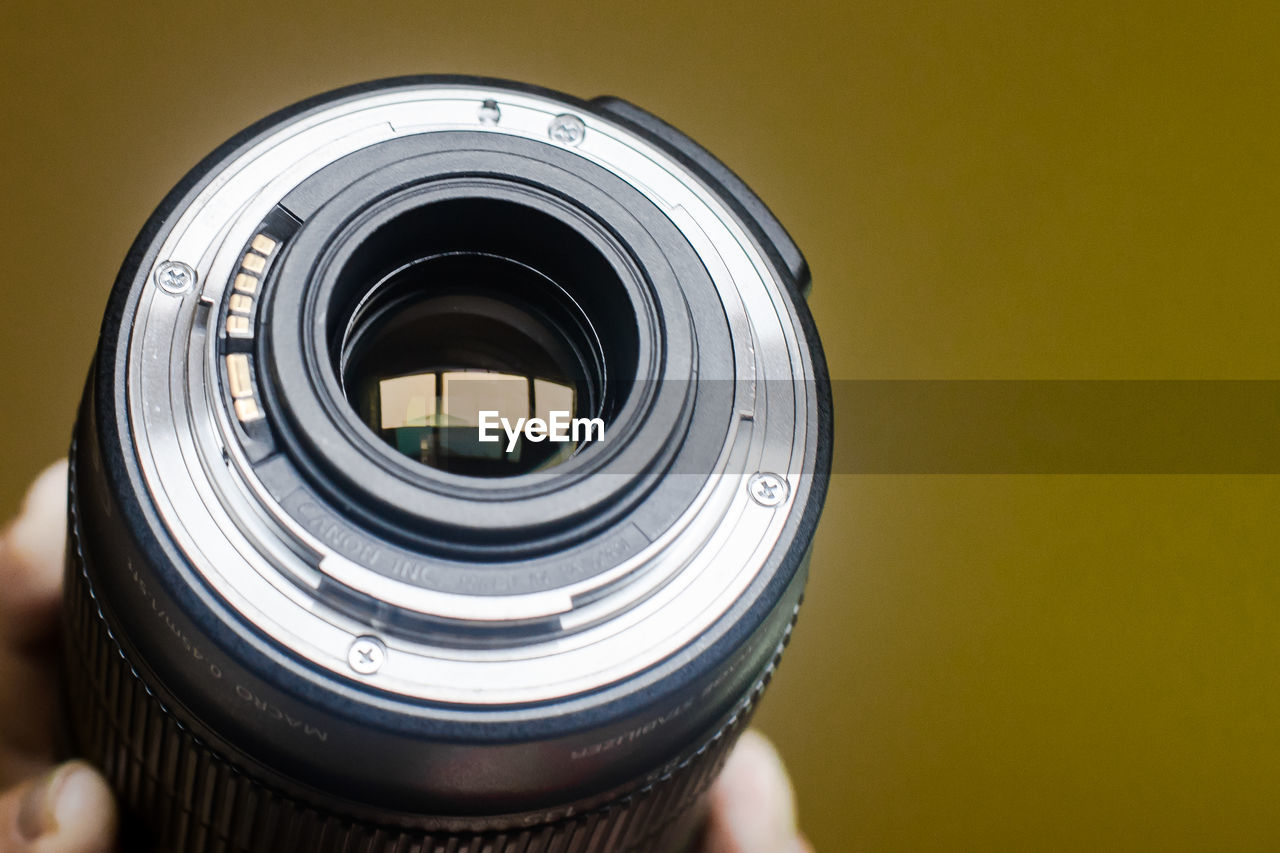 camera - photographic equipment, indoors, photography themes, close-up, technology, photographic equipment, geometric shape, circle, shape, lens - optical instrument, camera, studio shot, yellow, digital camera, real people, still life, human body part, modern, copy space, glass - material, silver colored, wheel