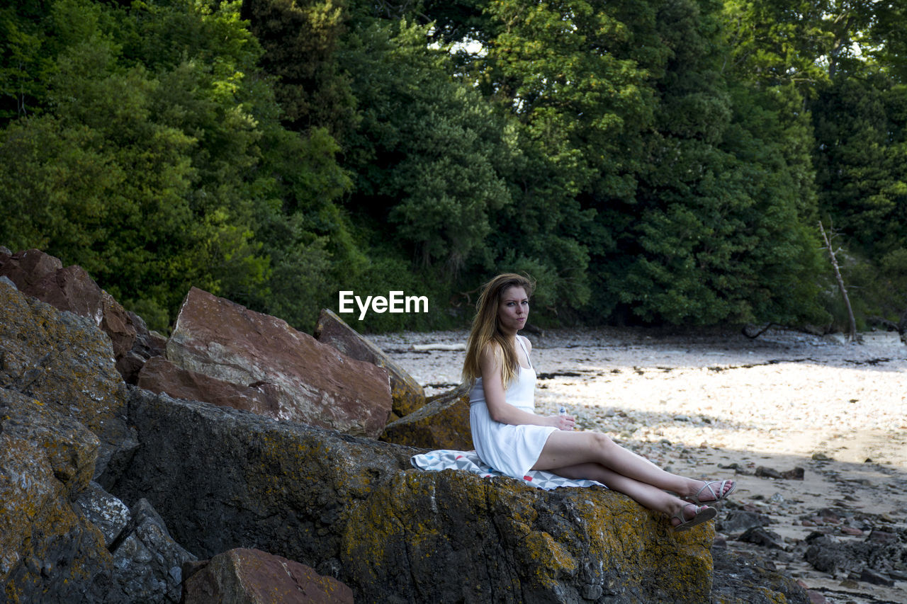 Portrait of young woman sitting on rock against trees