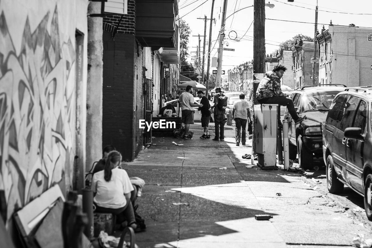 REAR VIEW OF PEOPLE WALKING ON STREET BY BUILDINGS