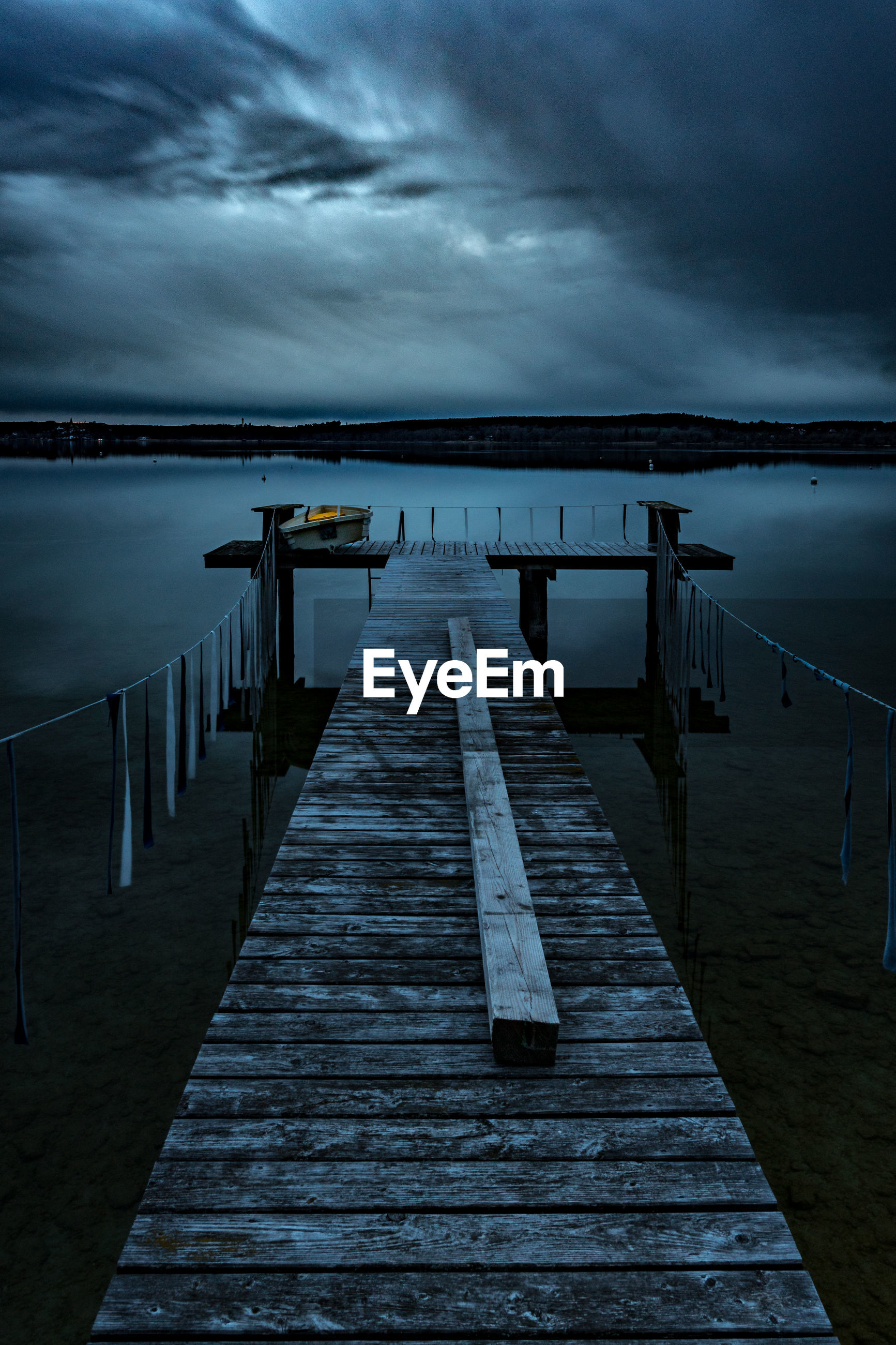 Wooden jetty over lake against sky at dusk