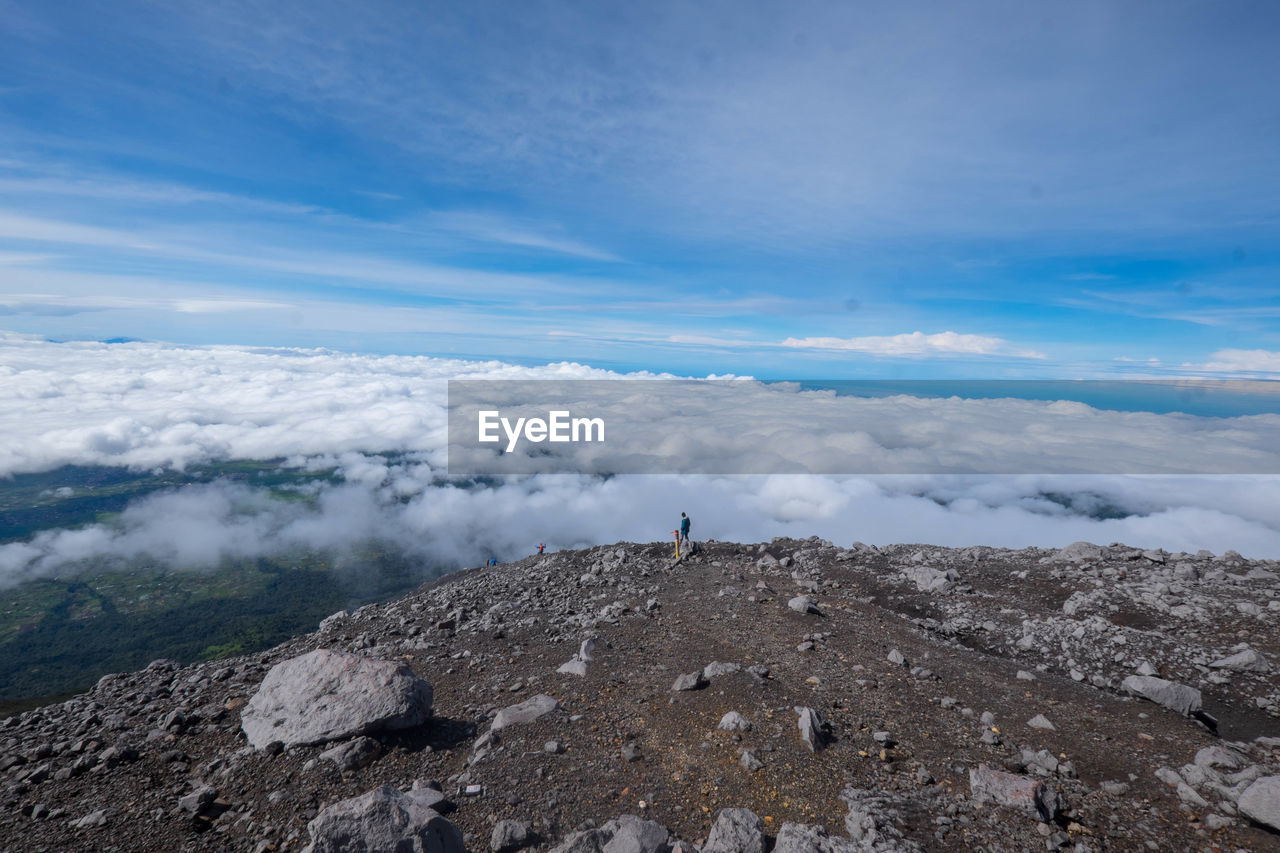 sky, cloud - sky, scenics - nature, beauty in nature, tranquility, tranquil scene, nature, rock, leisure activity, day, solid, mountain, rock - object, men, non-urban scene, one person, real people, unrecognizable person, lifestyles, adventure, outdoors