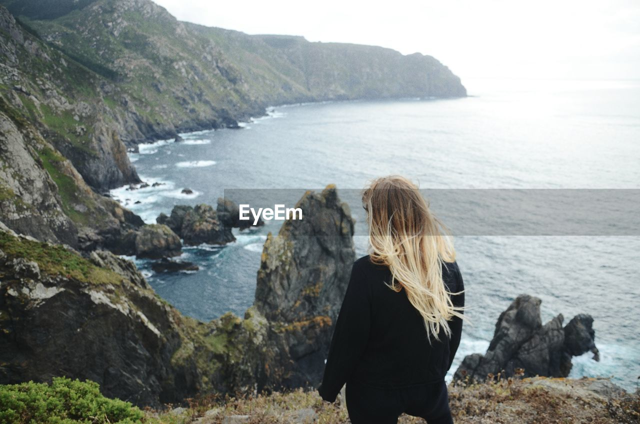 Rear view of woman standing on mountain by sea