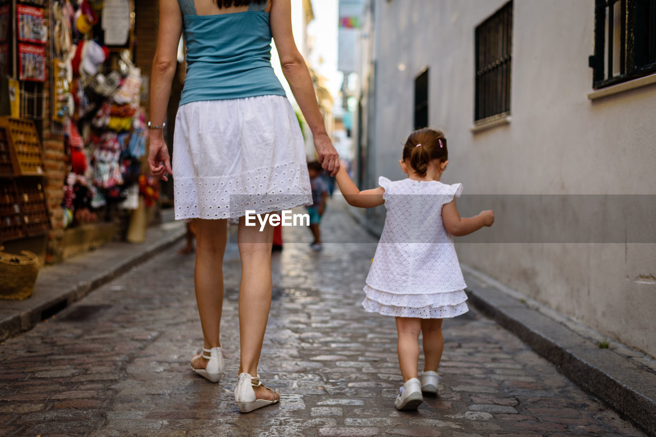 Low section of mother walking with daughter on street